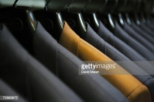 Row of hanging suits in wardrobe