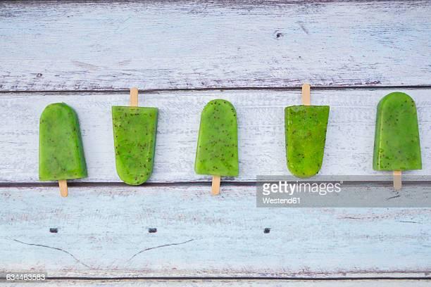 Row of homemade kiwi ice lollies on wood