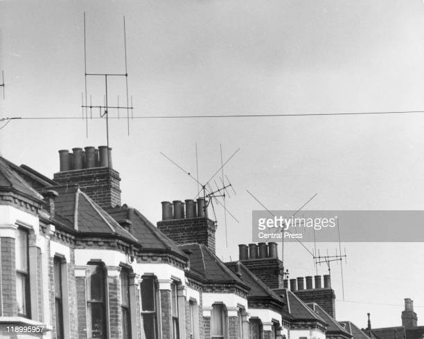 A row of houses each with a television aerial mounted on the chimney stack on the roof 1964