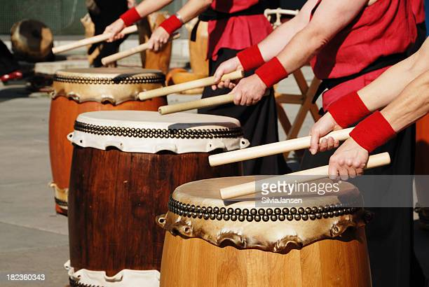 row of japanese drums and hands with sticks