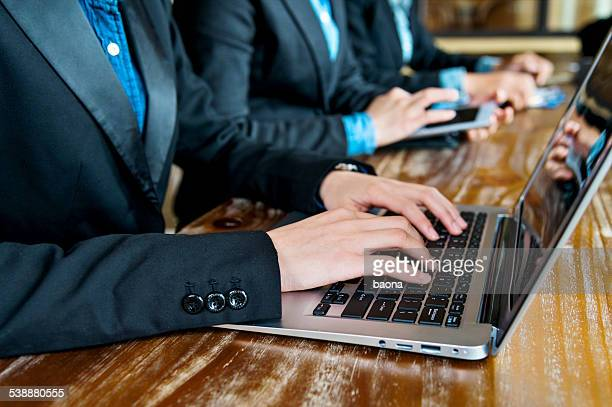 Row of laptops with hands