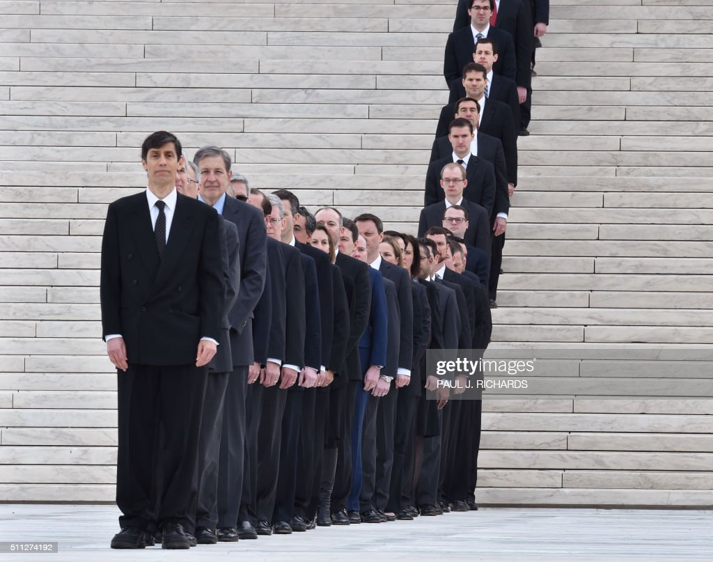 TOPSHOT - A row of Law clerks await to pay their respects during the arrival of US Justice Antonin Scalia's casket on the steps of the US Supreme Court February 19, 2016 in Washington, DC. /