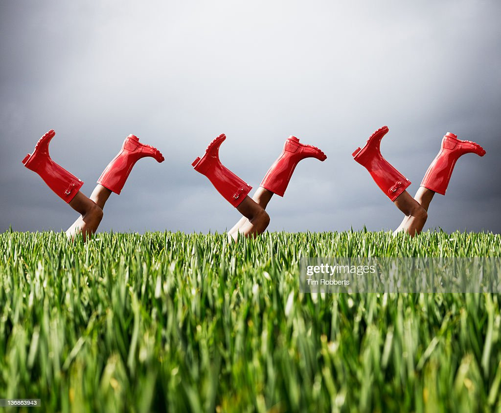 Row of legs in the air wearing red boots.