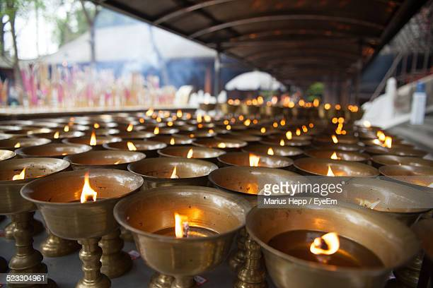 Row Of Lit Oil Lamps Arranged At Temple
