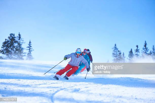Row of male and female skiers skiing down snow covered ski slope, Aspen, Colorado, USA
