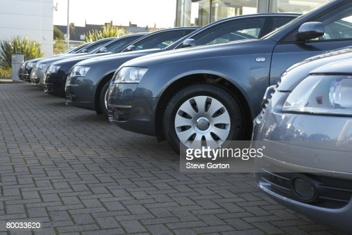 Row of metallic blue cars in car dealer's car park : Stock Photo