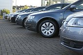 Row of metallic blue cars in car dealer's car park