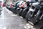 Row of motorcycles parked on wet street