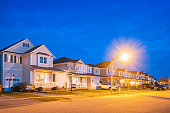 Stock photograph of a row of new homes in Brantford Ontario Canada, illuminated at twilight blue hour.