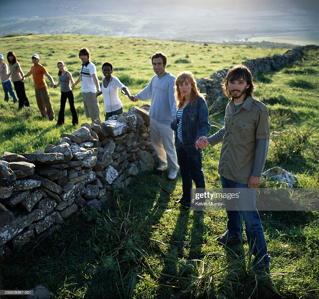 Row of people holding hands over dry stone wall, portrait : Stock Photo