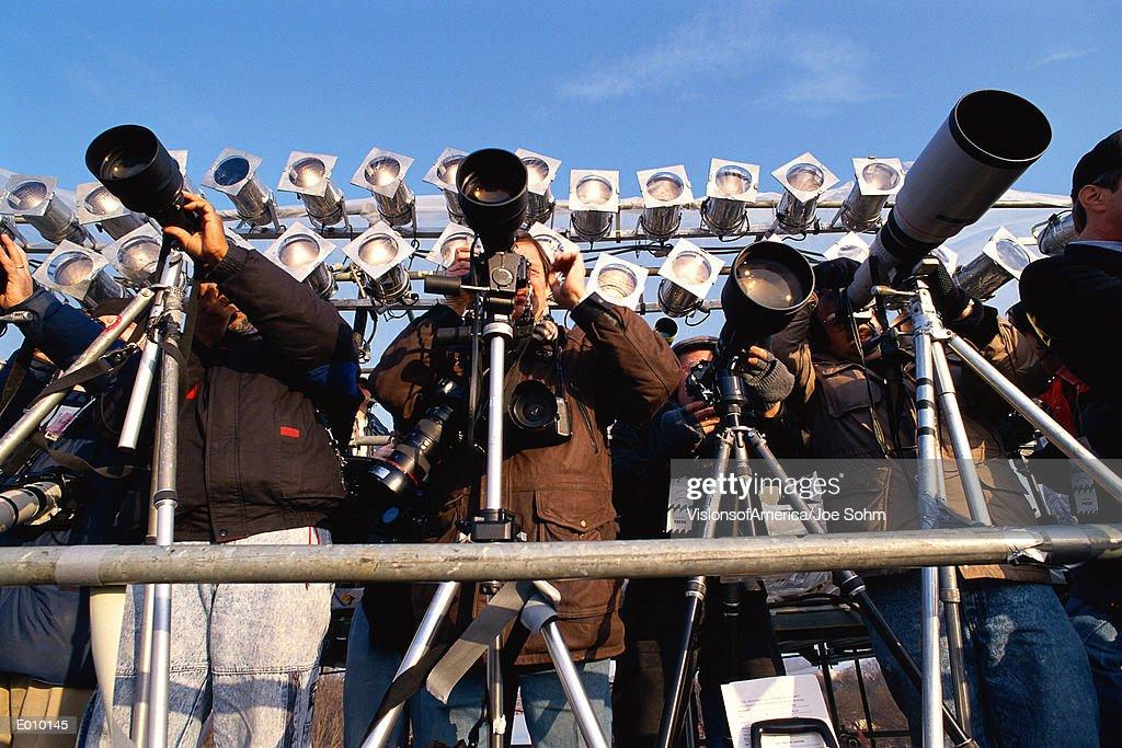 Row of photographers with telescopic lenses : Stock Photo