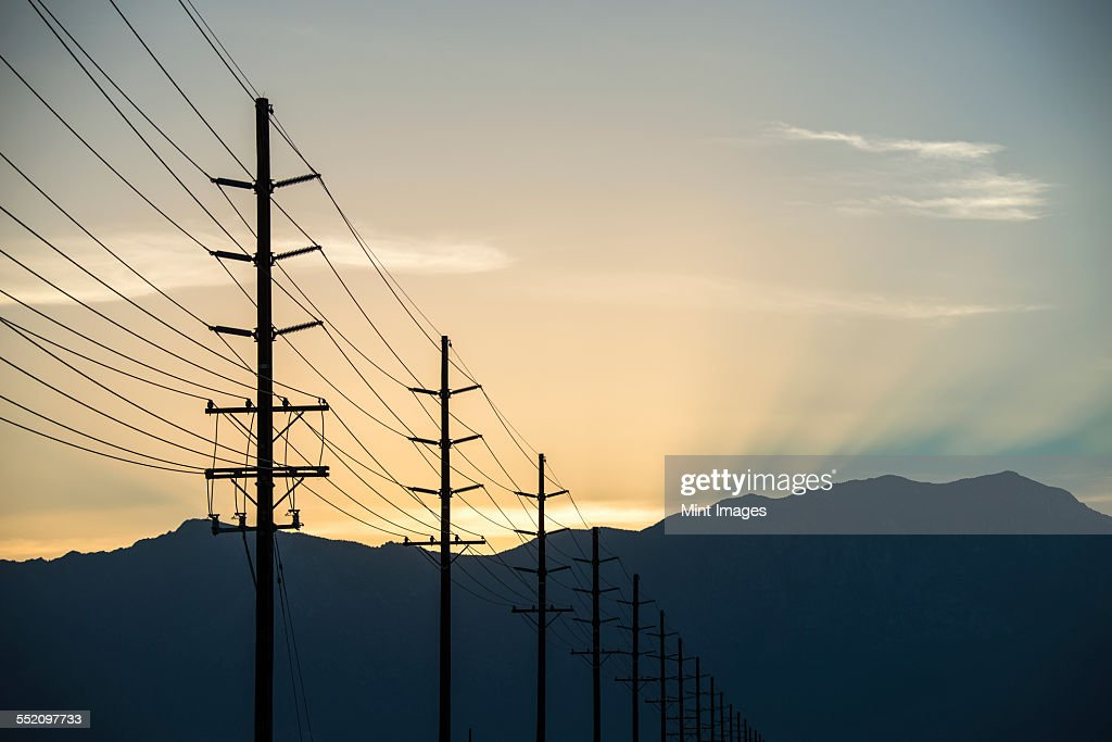 A row of poles and communication or power lines at sunset.