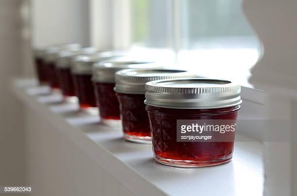 Row of red jam jars on window still