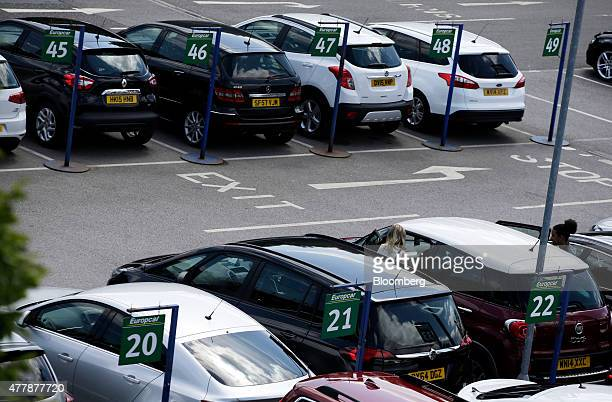 A row of rental cars are parked below Europcar Group SA parking bay signs at the Europcar location for Gatwick Airport in Crawley UK on Friday June...