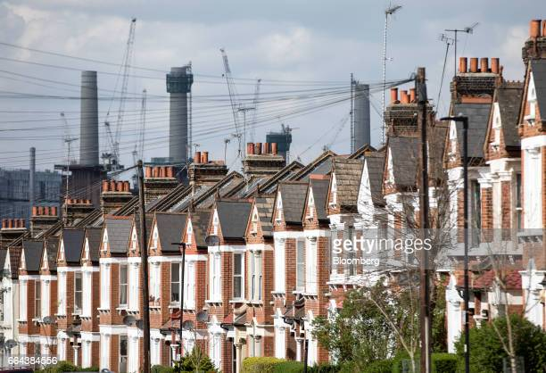 A row of residential properties stand in front of Battersea Power Station redevelopment in London UK on Monday April 3 2017 UK house prices fell for...