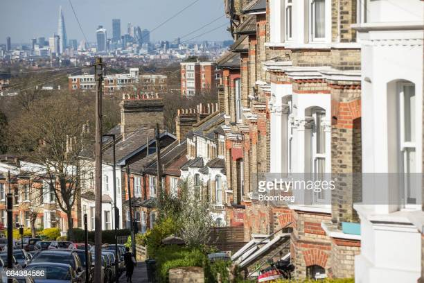 A row of residential terraced properties stand in front of the City of London financial district in London UK on Monday April 3 2017 UK house prices...