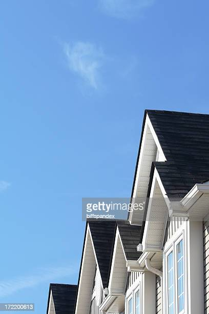 Row of roofs and eaves of homes with blue sky