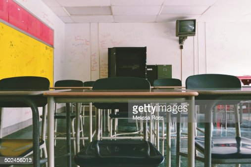 row of school desks in an abandoned classroom