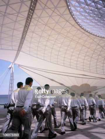 Row of security staff marching to work, Shanghai. : Stock Photo
