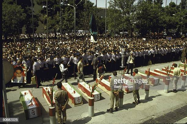 A row of shrouded caskets holding the victims of an Iranian Airbus accidently shot down by the USS Vincennes with a crowd of mourners behind them at...
