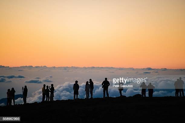 Row of silhouetted tourists above at sunset, Haleakala National Park, Maui, Hawaii