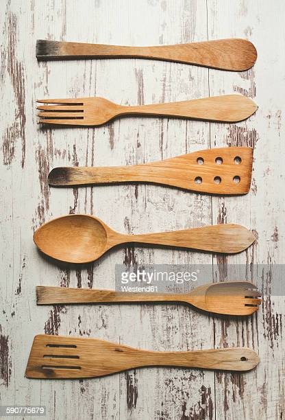 Row of six different wooden kitchen utensils on wooden background