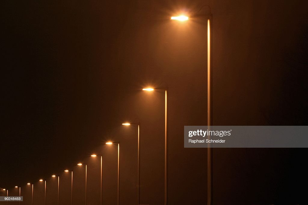 Row of street lamps at misty night forming a curve : Stock Photo