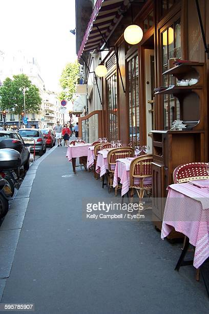 Row Of Tables And Chairs At Sidewalk Cafe In City