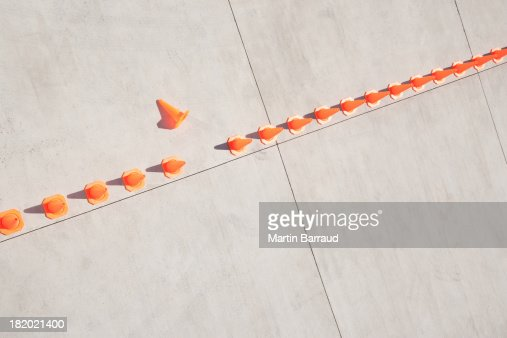 Row of traffic cones with one on side
