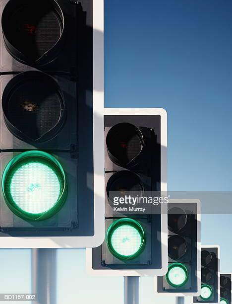 Row of traffic lights, green lights illuminated (Digital Composite)