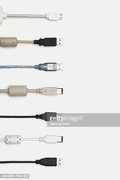 Row of USB, fire wire and computer cables, white background, overhead view