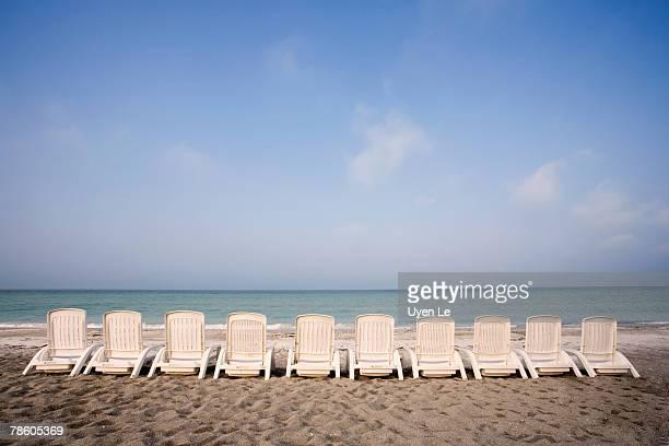 A row of white beach chairs line the beach along the Florida Gulf.  Longboat Key near Sarasota, Florida.