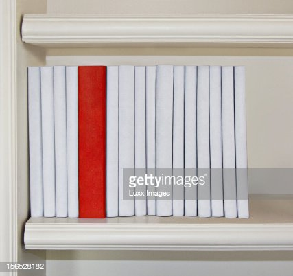 A row of white books with one red book : Stock Photo