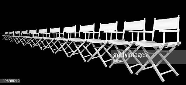 Row of white directors chairs on black background