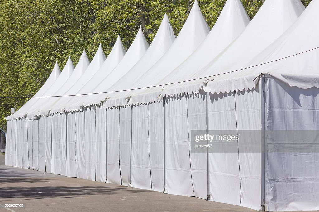 row of white tents on an empty Street among trees : Stock Photo