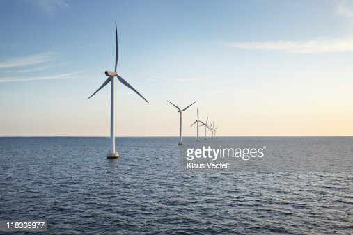 Row of winturbines in the sea shot in the sunset