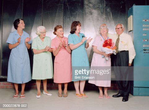Row of women in overalls applauding colleague receiving prize : Stock Photo