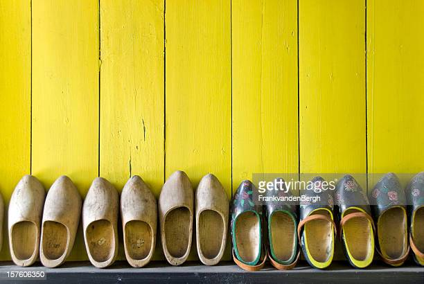Row of wooden shoes against a yellow wall