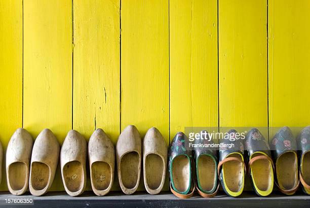 Rangée de chaussures en bois contre un mur jaune