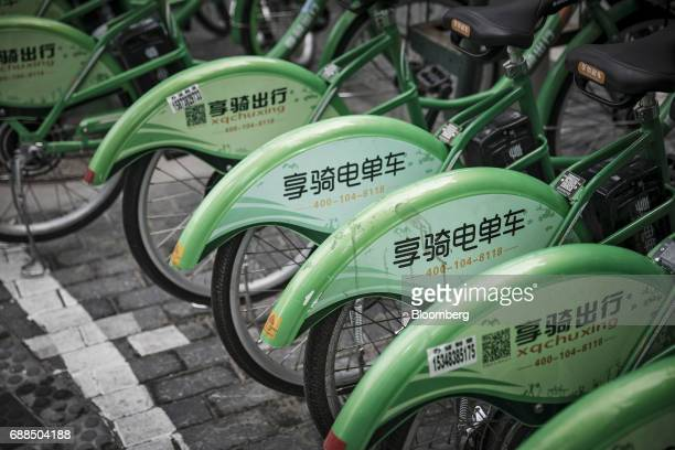 A row of Xiangqi Chuxing electric bicycles stand parked on a sidewalk in Shanghai China on Thursday May 25 2017 In China a bicyclesharing phenomenon...