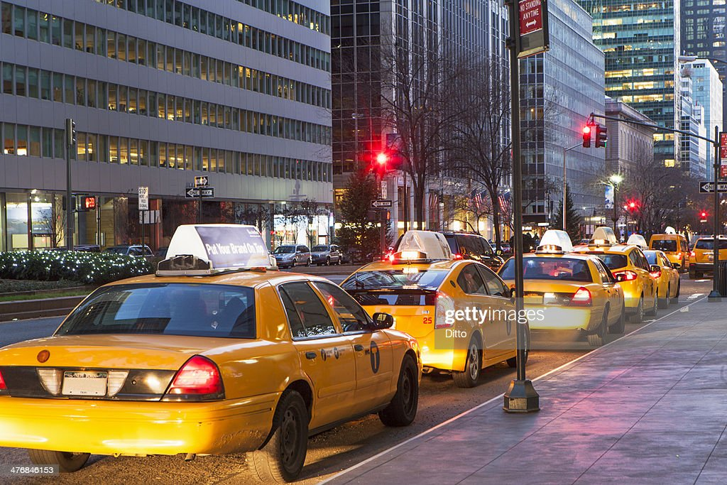 Row of yellow cabs next to sidewalk, New York, USA