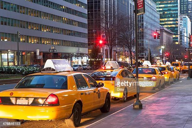 Row of yellow cabs next to sidewalk, New York, USA
