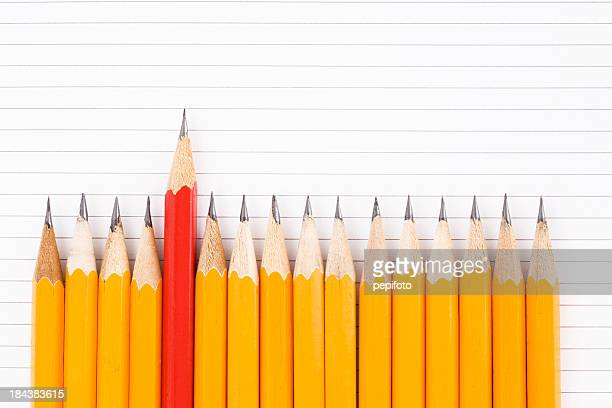 Row of yellow pencils with a red one sticking out