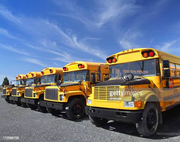 Row of yellow school buses against partly cloudy sky