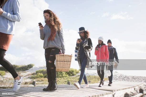Row of young adult friends strolling along beach boardwalk reading smartphones, Western Cape, South Africa