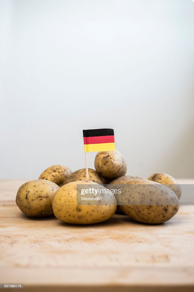 Row potatoes and small german little flag on wood