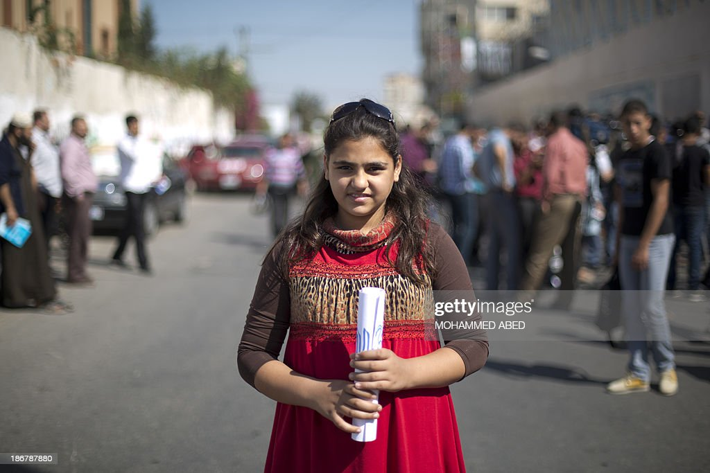 Rowan Salti, 13, participates in a rally in front of United Nations Relief and Work Agency (UNRWA) in Gaza City, on October 28 , 2013. Salti fler her home in the Yarmuk refugee camp in Syria in August 2011 after the camp was bombed by government forces. She left Damascus along with her family by plane to Cairo then crossed into the Gaza Strip through the Rafah crossing terminal. She is currently attending school.