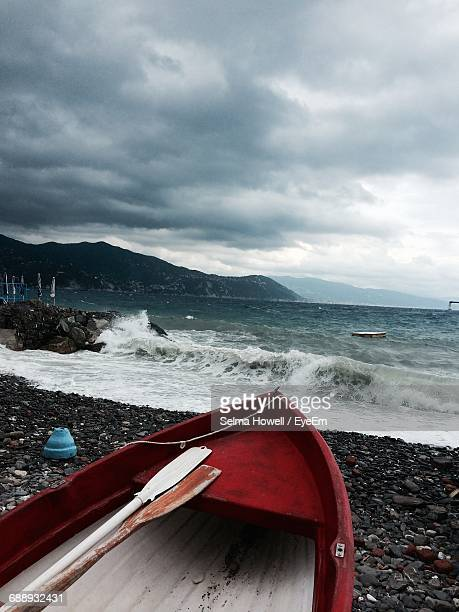 Rowboat Moored At Beach Against Cloudy Sky