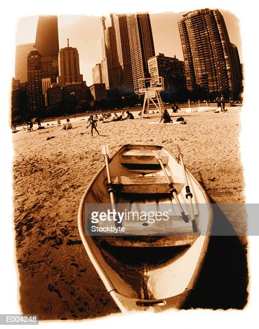 Rowboat stranded on beach, city behind : Stock Photo