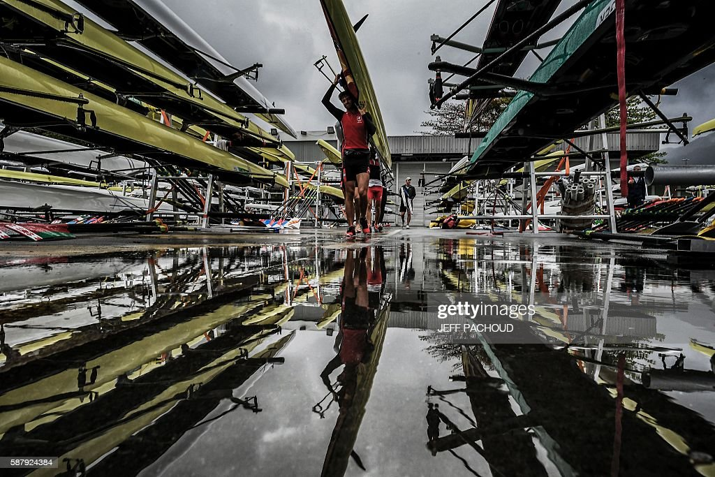 TOPSHOT - Rowers carry their boats after a training session at the Lagoa stadium following the cancellation the day's races due to bad weather condition during the Rio 2016 Olympic Games in Rio de Janeiro on August 10, 2016. / AFP / JEFF